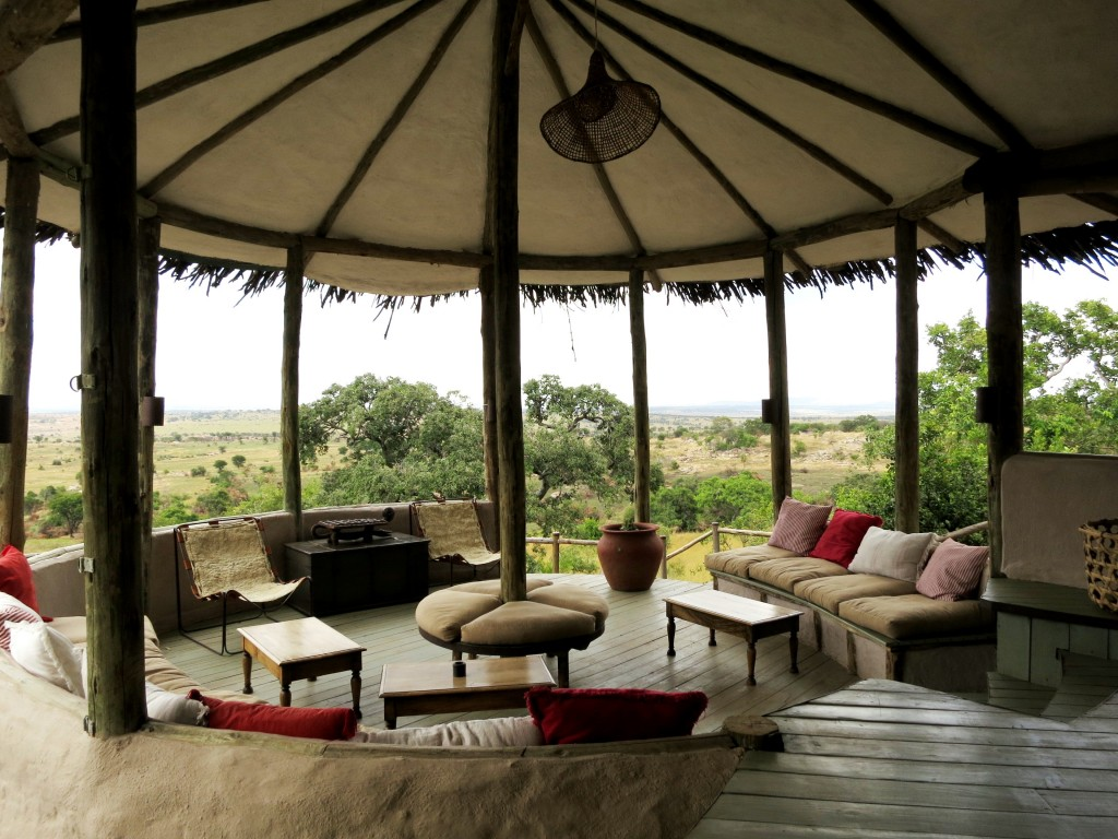 The reception area at Lamai Serengeti is decorated with colorful throw pillows and looks out to the rolling hills of Kenya