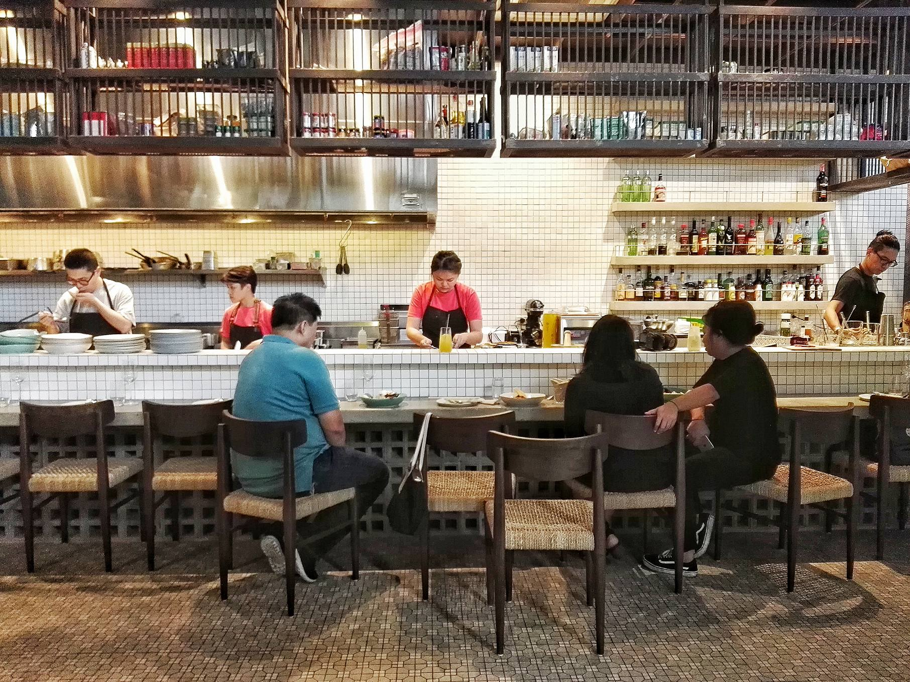An open kitchen set against a white-tiled wall and intentionally chipped in patterned flooring feature in Hey Handsome in Bonifacio Global City, the second restaurant from the folks behind Your Local